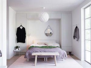 Snyggt inredd garderob runt säng