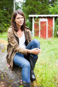 Åsa Avdic porträtt sitter på en sten