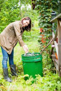 Åsa Avdic fyller på vattenkannan i trädgården