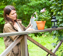 Åsa Avdic vattnar en krukväxt i trädgården