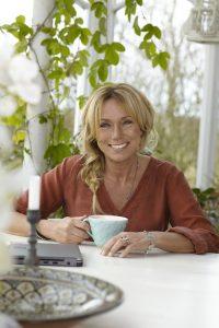 Anne Lundberg med en kopp kaffe i sitt orangeri