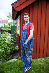 Micke Leijnegard står vid stugans husknut