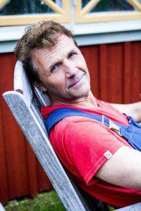 Micke Leijnegard i solstol utanför stugan